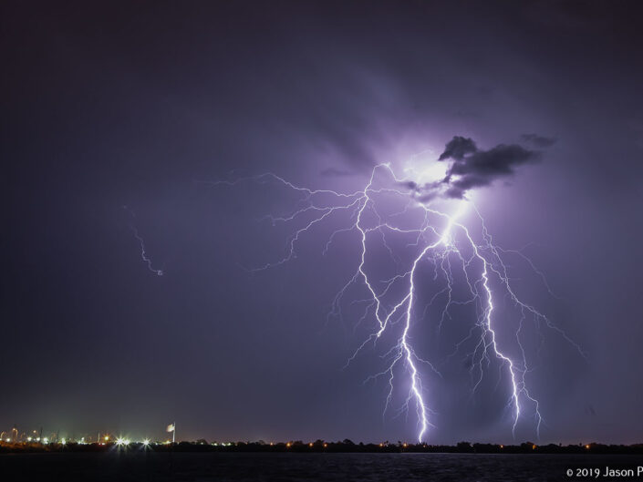 A powerful bolt of lightning strikes Merritt Island, Florida during an evening thunderstorm.