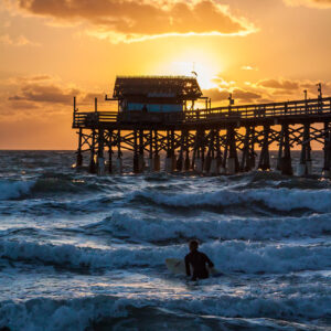 A surfer wades out into the ocean at the Cocoa Beach Pier for a quick surf at sunrise.