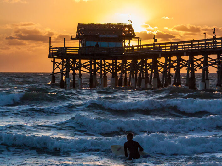 A surfer at the world-famous Cocoa Beach Pier in Florida takes to the water at sunrise.